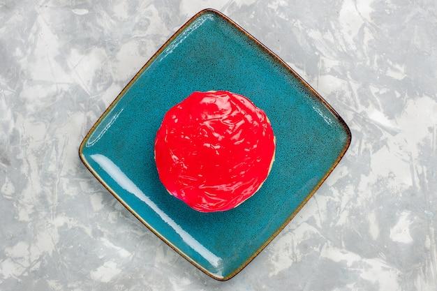 Вид сверху восхитительно выглядящий торт маленький пирог с красным кремом на светло-белой поверхности торт бисквит выпечка крем сахар сладкий