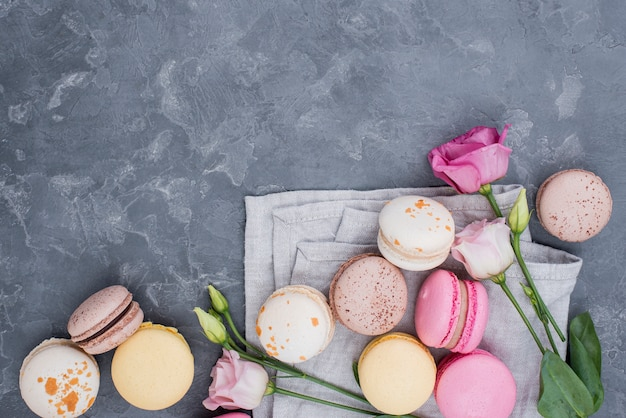 Top view of delicious macarons with roses and copy space