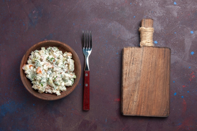 Вид сверху вкусный салат майонез с курицей внутри коричневой тарелки на темном пространстве