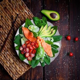 Еда взгляд сверху очень вкусная в плите с палочками и авокадоом на деревянной предпосылке.