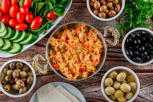Вид сверху вкусная еда в горшочке с салатом, солеными огурцами в мисках на деревянной поверхности