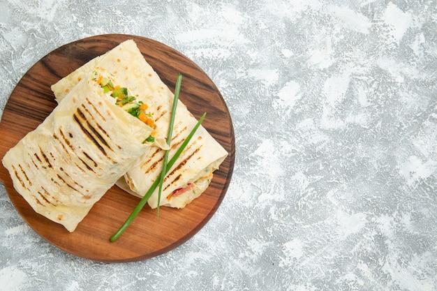 Vista dall'alto delizioso pasto panino a base di carne alla griglia allo spiedo affettato su uno spazio bianco
