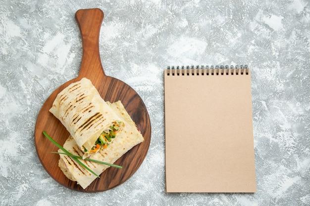 Вид сверху вкусный бутерброд с едой, приготовленный на гриле на вертеле, нарезанный на белом пространстве