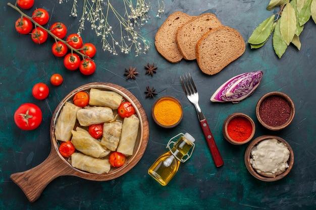 トップビューおいしい肉料理をキャベツの中に巻き、紺色の机の上にオイルパンとフレッシュトマトを添えて肉料理ディナーカロリー野菜料理