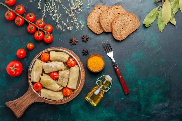 上面図紺色の机の上に油パンとフレッシュトマトを添えてキャベツに巻いた美味しい肉料理夕食カロリー野菜料理