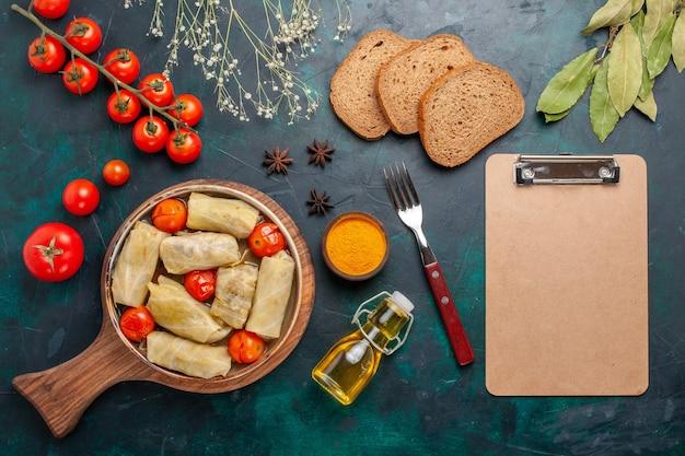 上面図紺色の机の上に油パンとフレッシュトマトを添えてキャベツに巻いた美味しい肉料理