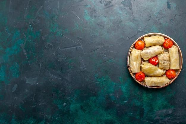 Vista dall'alto delizioso pasto a base di carne arrotolato all'interno del cavolo con pomodori sul piatto di cottura di verdure caloriche della cena del cibo della carne della scrivania blu scuro
