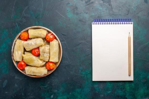 Vista dall'alto delizioso pasto di carne arrotolato all'interno di cavolo con pomodori e blocco note sulla scrivania blu scuro carne cibo cena calorie cucina vegetale