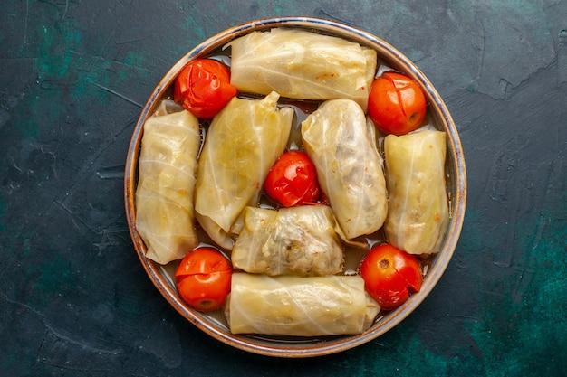 Вид сверху вкусной мясной еды, завернутой в капусту с помидорами на темно-синем столе, мясная еда, ужин, калорийность, овощная кулинария