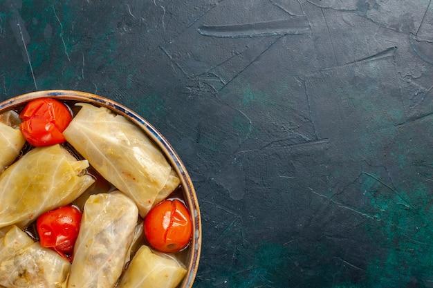上面図紺色の机の上にトマトとキャベツの中で巻いたおいしい肉骨粉肉骨粉夕食カロリー野菜料理