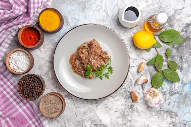 Vista dall'alto deliziosa farina di carne con salsa e condimenti su piatto di carne da tavola bianca