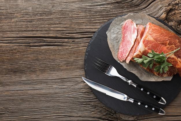 Вид сверху вкусного мяса на тарелку со столовыми приборами