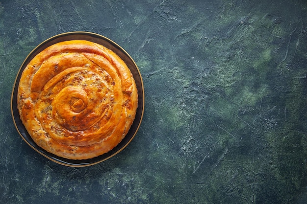 Top view of delicious meat pie on dark surface