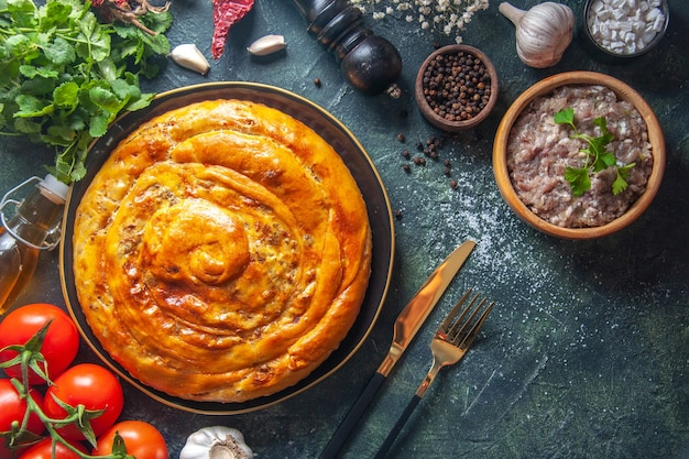 Top view of delicious meat pie with ingredients on dark surface