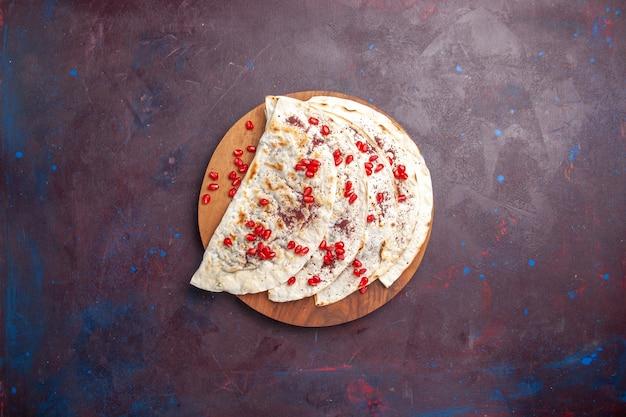 Vista dall'alto deliziose qutab di carne pitas con melograni freschi su pita di pasta di carne superficie viola scuro