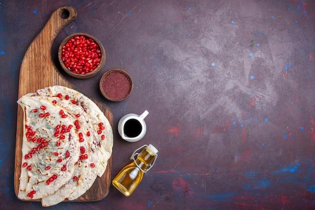トップビューおいしい肉クタブピタと新鮮な赤いザクロの暗い机の上の生地ミールフードピタ