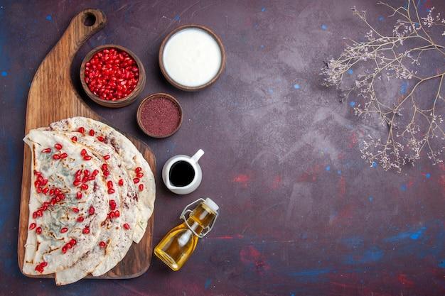 暗い床に新鮮な赤いザクロを添えたおいしい肉クタブピタの上面図生地ミールフードピタ