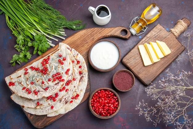 上面図暗い表面に新鮮な赤いザクロが付いたおいしい肉クタブピタ生地ミールフードピタ