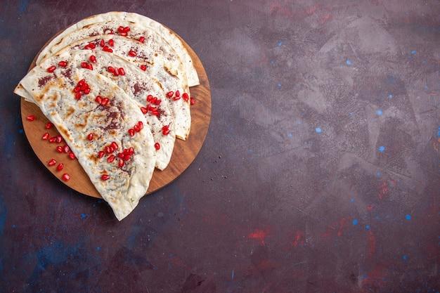 어두운 보라색 배경 고기 반죽 식사 피타에 빨간 석류와 상위 뷰 맛있는 고기 qutabs pitas