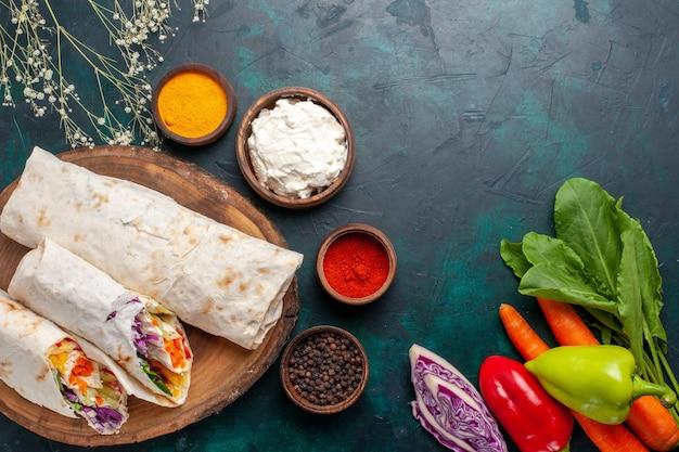 상위 뷰 맛있는 고기 샌드위치 진한 파란색 책상에 신선한 야채와 함께 침에 구운 고기로 만든 샌드위치 햄버거 음식 식사 점심 고기