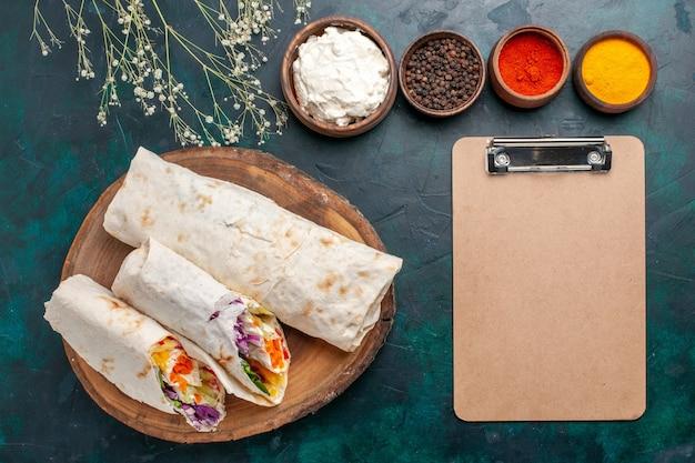 상위 뷰 맛있는 고기 샌드위치 진한 파란색 책상 샌드위치 햄버거 고기 음식 식사 점심에 조미료와 함께 침에 구운 고기로 만든 샌드위치