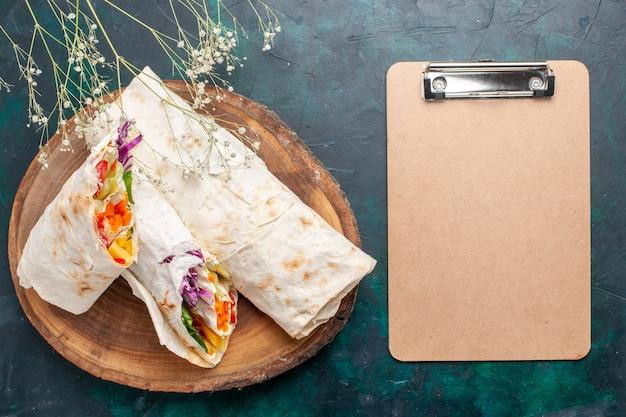 Vista dall'alto delizioso panino di carne fatto di carne alla griglia allo spiedo affettato con blocco note sulla scrivania blu scuro hamburger pasto a base di carne pranzo cibo sandwich