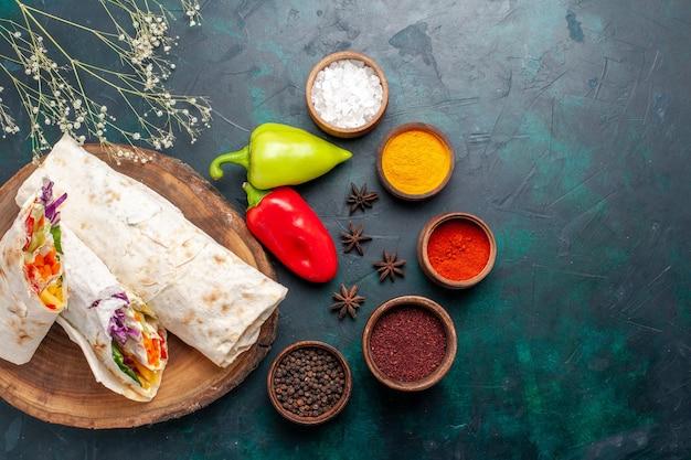 Vista dall'alto delizioso panino di carne fatto di carne alla griglia allo spiedo affettato con condimenti su sfondo blu hamburger pasto a base di carne pranzo panino