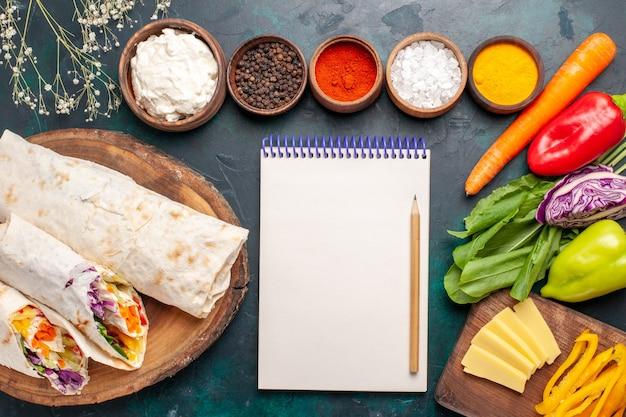 Vista dall'alto delizioso panino di carne fatto di carne alla griglia allo spiedo con condimenti e verdure sulla scrivania blu panino hamburger carne cibo pasto pranzo