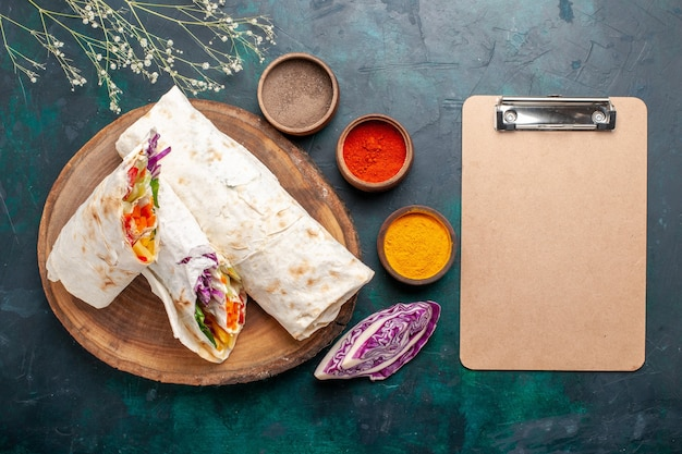 Вид сверху вкусный мясной бутерброд из мяса, приготовленного на гриле на вертеле, нарезанный блокнотом и приправами на синем столе, бургер, мясная еда, обед, еда, бутерброд