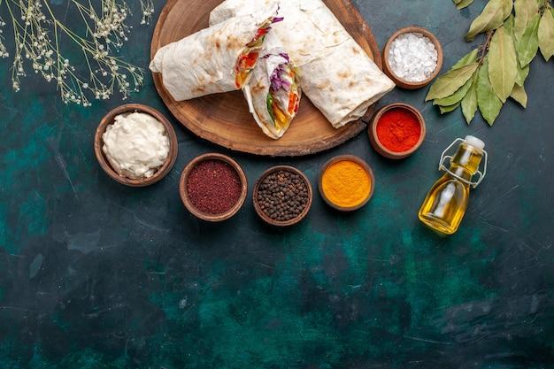 Вид сверху вкусный мясной бутерброд из мяса, приготовленного на вертеле, нарезанного маслом и приправами на синем столе, бургер, мясная еда, обед, сэндвич, еда