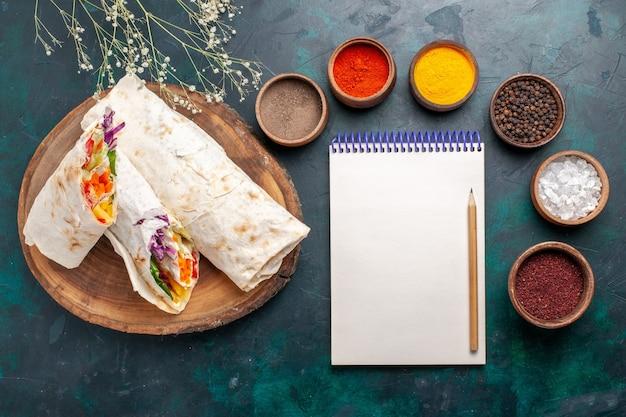 Вид сверху вкусный мясной сэндвич из мяса, приготовленного на вертеле, нарезанного с приправами на синем столе, бургер, мясная еда, обед, бутерброд