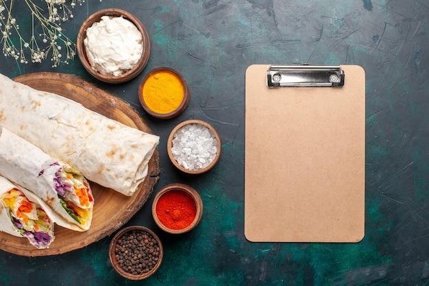 上面図おいしい肉サンドイッチは、青い机のサンドイッチに調味料とメモ帳を添えて串で焼いた肉でできています