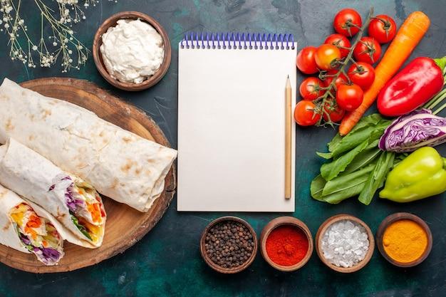 Вид сверху вкусный мясной сэндвич из мяса, приготовленного на вертеле с приправами и овощами на синем фоне, сэндвич, гамбургер, мясная еда, обед