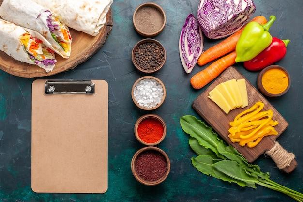 上面図青い机の上に調味料と野菜を添えて串焼きにした肉で作ったおいしいミートサンドイッチハンバーガーミートミールランチフードサンドイッチ