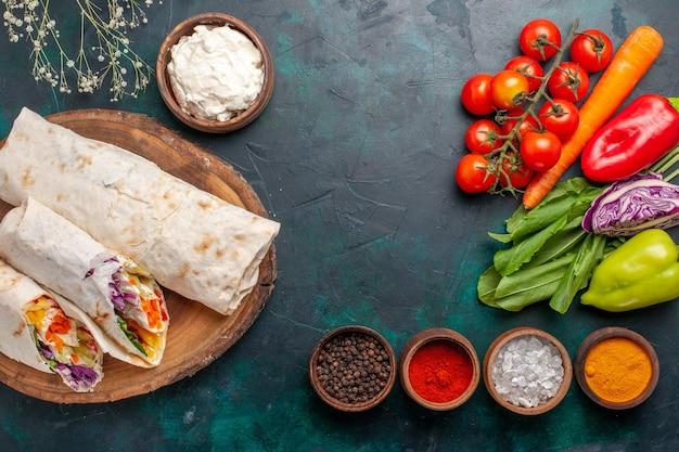 Вид сверху вкусный мясной бутерброд из мяса, приготовленного на вертеле с приправами и овощами на синем столе сэндвич бургер мясная еда обед
