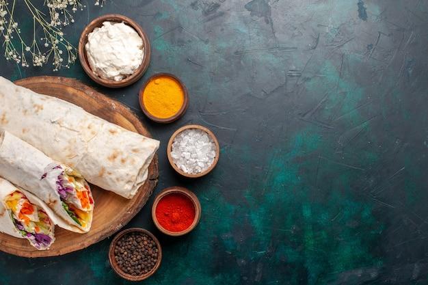 Вид сверху вкусный мясной бутерброд из мяса, приготовленного на вертеле с приправами на синем фоне, сэндвич, бургер, мясная еда, обед, еда