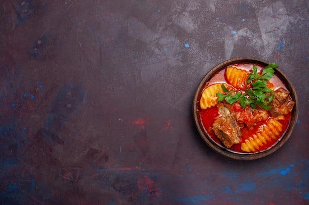 Vista dall'alto deliziosa zuppa di sugo di carne con verdure e patate a fette su una superficie scura salsa di zuppa pasto piatto per cena