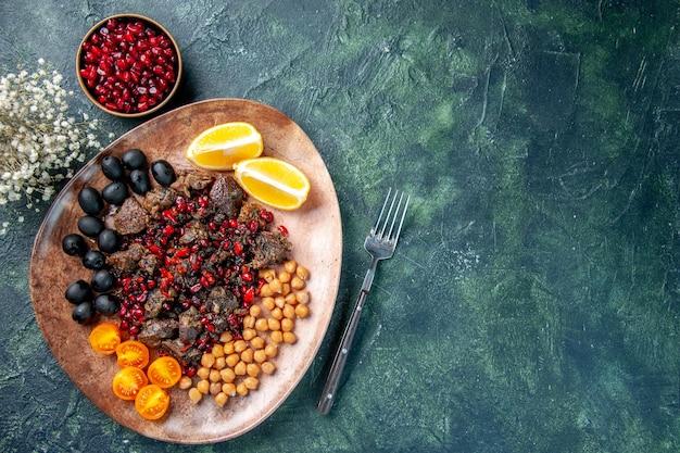 Вид сверху вкусные кусочки мяса, обжаренные с фасолью, виноград и ломтики лимона внутри тарелки, еда, фрукты, мясо, блюдо, еда