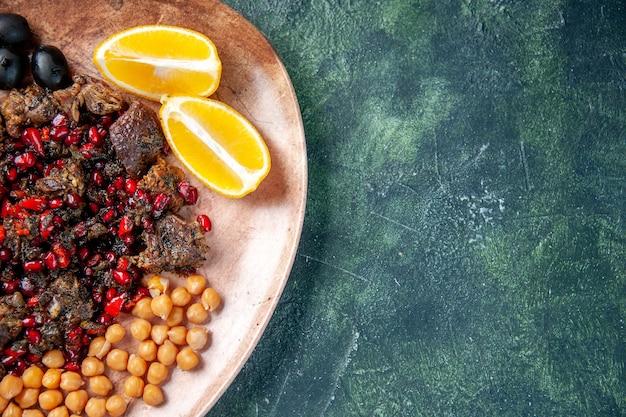 Вид сверху вкусные кусочки мяса, обжаренные с фасолью, виноград и ломтики лимона внутри тарелки