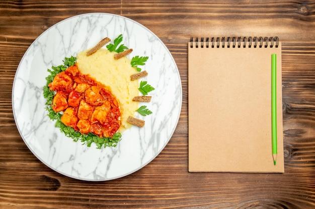 Вид сверху вкусные кусочки мяса с картофельным пюре и зеленью на деревянном столе, мясная хлебная мука, картофельное блюдо