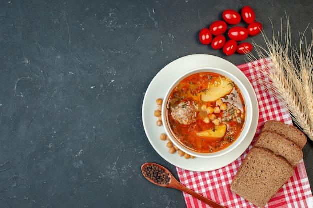 トップビューおいしい肉汁は、暗い背景にジャガイモと肉で構成されています