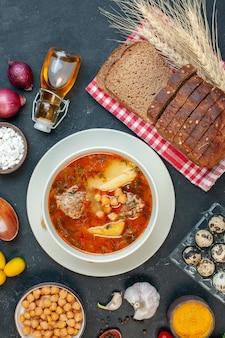 トップビューおいしい肉汁は、暗い背景にジャガイモの肉と豆で構成されています