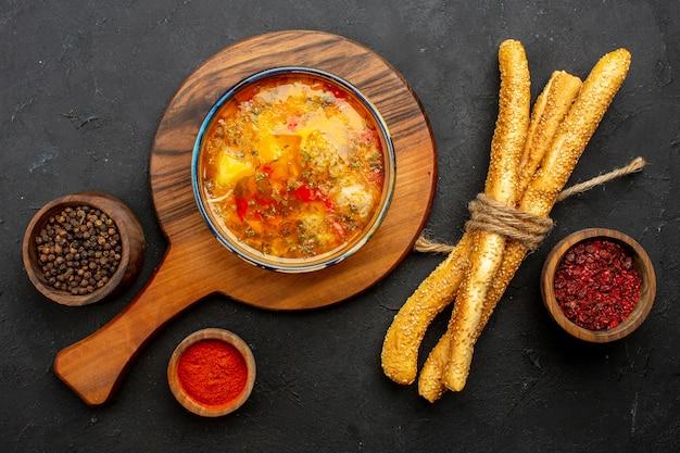 灰色の空間にパンと調味料が入った上から見た美味しい肉スープ
