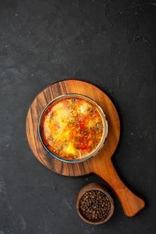 Вид сверху вкусного мясного супа с вареным картофелем и мясом на темно-сером пространстве