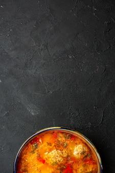 어두운 회색 공간에 요리 된 감자와 고기가 들어간 맛있는 고기 수프