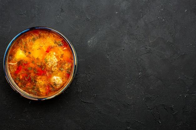 灰色の空間に調理されたジャガイモと肉が入ったトップビューのおいしい肉スープ