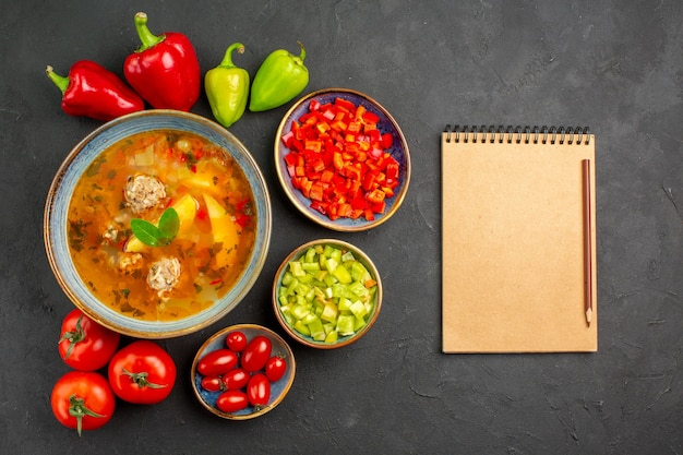 Vista dall'alto una deliziosa zuppa di carne con verdure fresche sul cibo pasto foto piatto tavolo scuro Foto Gratuite