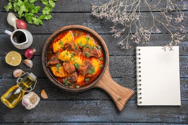 Vista dall'alto una deliziosa zuppa di carne con patate e verdure sulla scrivania scura