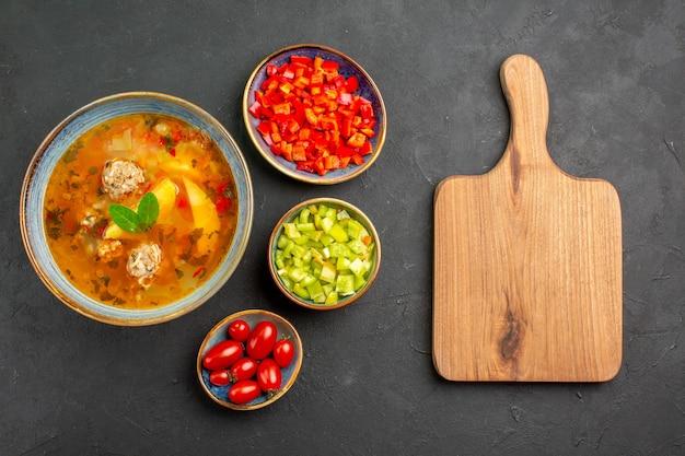 Vista dall'alto una deliziosa zuppa di carne con pepe a fette sul cibo pasto foto piatto tavolo scuro Foto Gratuite