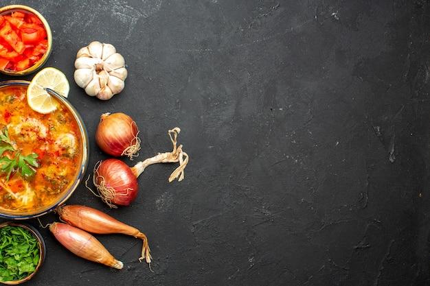 Vista dall'alto una deliziosa zuppa di carne con verdure a fette sullo spazio grigio